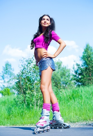 skate park: happy young brunette woman on roller skates in the park