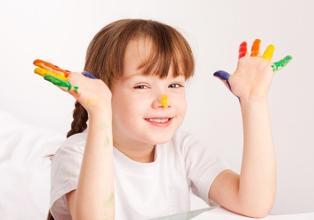 happy cute five year old girl sitting by the table and  painting with watercolor at home Stock Photo - 9613754