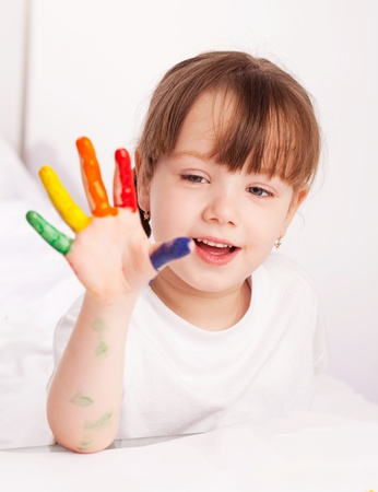 happy cute five year old girl sitting by the table and  painting with watercolor at home Stock Photo - 9613780