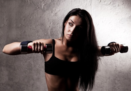 female sexuality: beautiful sporty muscular woman with two dumbbell in the gym