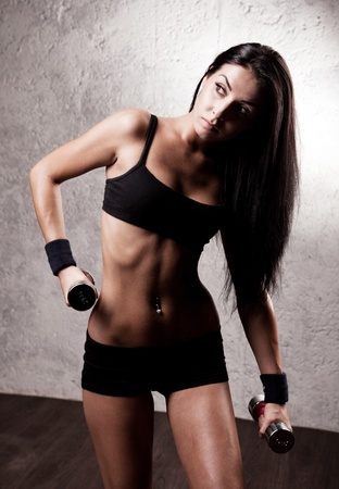 beautiful sporty muscular woman with two dumbbell in the gym photo