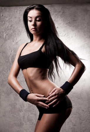 female sexuality: beautiful young sporty muscular woman with long hair in the gym against the old wall