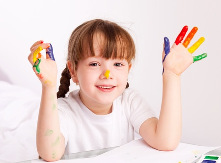 happy cute five year old girl sitting by the table and  painting with watercolor at home Stock Photo - 9617690
