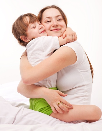 sleeping girl: beautiful young mother and her five year old daughter on the bed at home