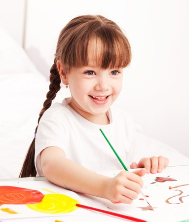 happy cute five year old girl sitting by the table and  painting with watercolor at home Stock Photo - 9617692