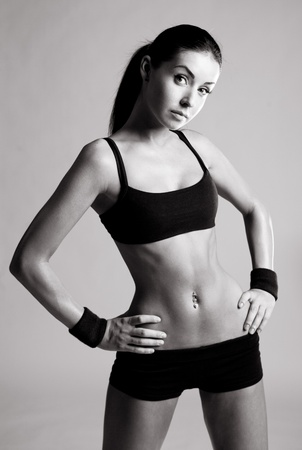 female bodybuilder: black and white portrait of a beautiful young sporty muscular  woman, isolated against white background