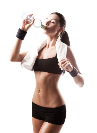 female body: sporty muscular  woman drinking water, isolated against white background
