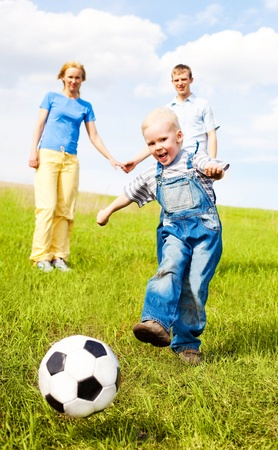 happy young family playing football outdoor on a summer day Stock Photo - 9617966