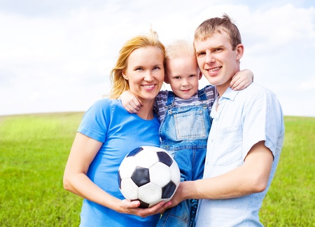 happy young family playing football outdoor on a summer day Stock Photo - 9617967