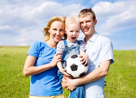 happy young family playing football outdoor on a summer day photo