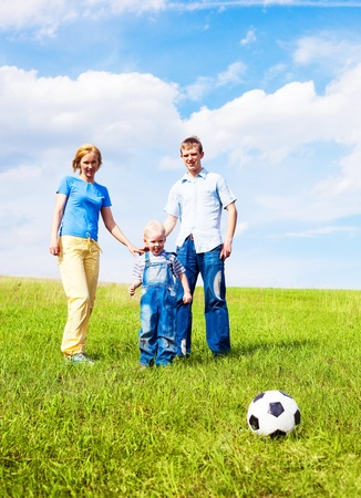 happy young family playing football outdoor on a summer day Stock Photo - 9618039