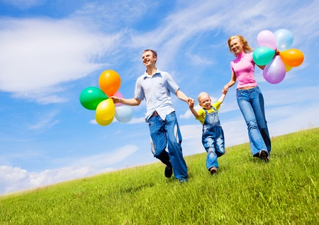 happy family walking with balloons outdoor on a warm summer day Stock Photo - 9617947