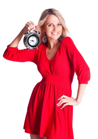 beautiful happy young blond woman holding an alarm clock, isolated against white background photo