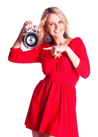 beautiful happy young blond woman pointing to the alarm clock, isolated against white background photo