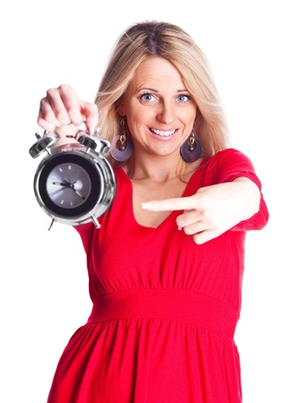 young blond woman pointing to the alarm clock, isolated against white background photo