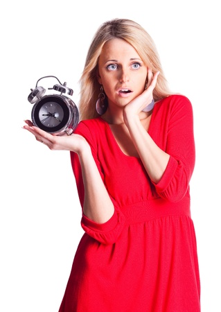 young blond woman holding the alarm clock, isolated against white background photo