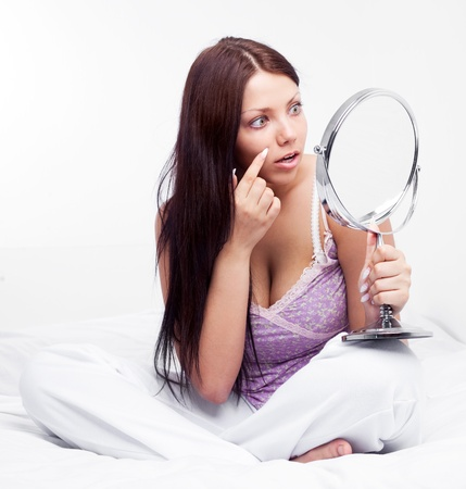 beautiful worried brunette woman with a mirror  on the bed at home photo