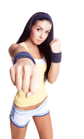 beautiful young brunette woman wearing sports clothes,  practicing fighting photo