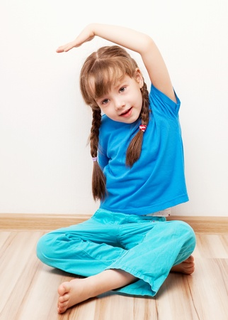 five year old: beautiful five year old girl stretching the muscles of her back and  arms at home Stock Photo