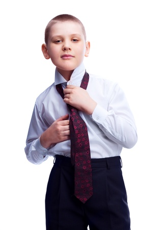 ten year old blond boy putting on a costume and a tie , isolated against white photo