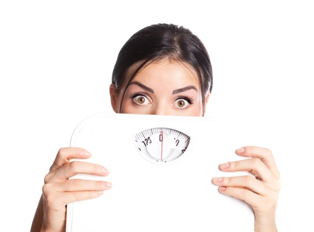 beautiful young scared  woman  holding scales, isolated against white background   photo