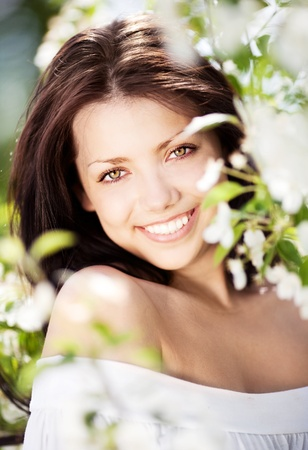 outsides: beautiful young brunette woman standing near the apple tree Stock Photo