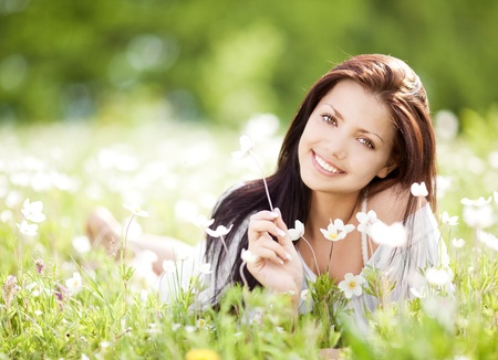 on pasture: beautiful young brunette woman  on the  meadow with white flowers  on a warm summer day Stock Photo