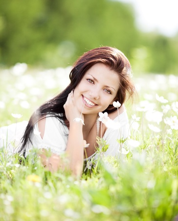 summertime: beautiful young brunette woman  on the  meadow with white flowers  on a warm summer day Stock Photo