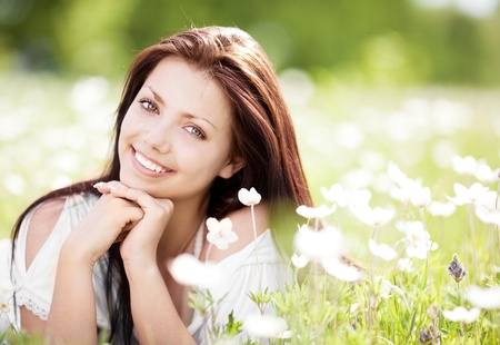 beautiful young brunette woman  on the  meadow with white flowers  on a warm summer day Stock Photo - 9753500