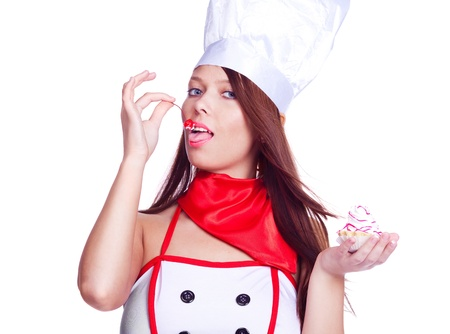 sexy brunette cook wearing uniform and eating  the cake with cream and a cherry on the top, isolated against white background photo