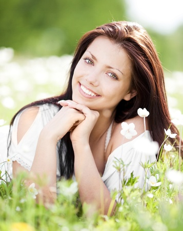 beautiful young brunette woman  on the  meadow with white flowers  on a warm summer day Stock Photo