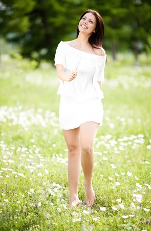 beautiful young brunette woman  on the  meadow with white flowers  on a warm summer day photo