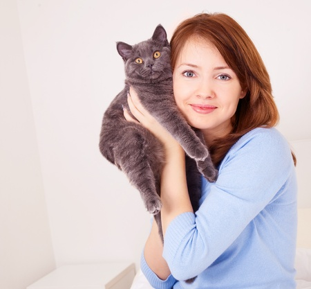 pretty young woman with her cat on the bed at home Stock Photo - 9757127