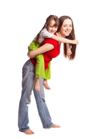 piggyback ride: happy young family; mother and her daughter  isolated against white background (focus on the woman)
