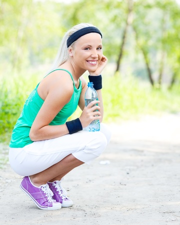 beautiful young blond sporty woman running in the park on a warm summer day and drinking water photo