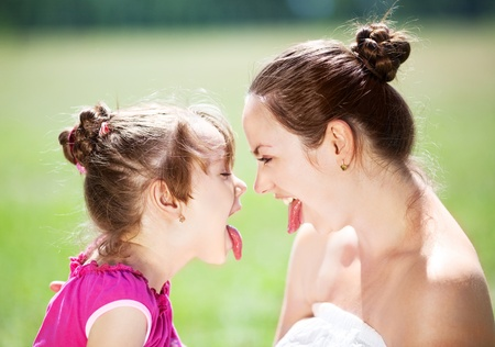 beautiful young mother and her daughter in the park on a sunny summer day  having fun and showing tongue (focus on the woman)