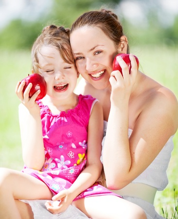 beautiful young mother and her daughter eating apples in the park on a sunny summer day (focus on the woman) photo