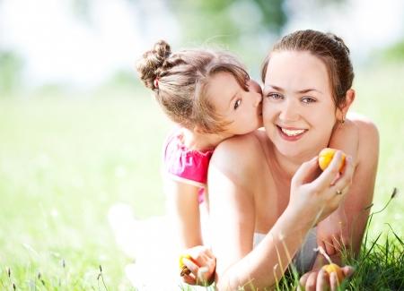 hermosa joven madre y su hija comer peras en el parque en un día soleado de verano (enfoque en la mujer)