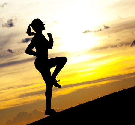 Silhouette of a beautiful woman running up the hill against yellow sky with clouds at sunset Stock Photo - 9757582
