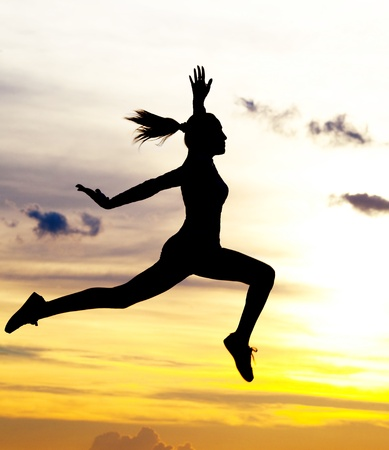 Silhouette of a beautiful jumping woman against yellow sky with clouds at sunset Stock Photo - 9757633