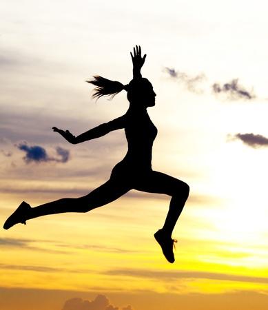 jumping: Silueta de una hermosa mujer salta contra cielo amarillo con nubes al atardecer