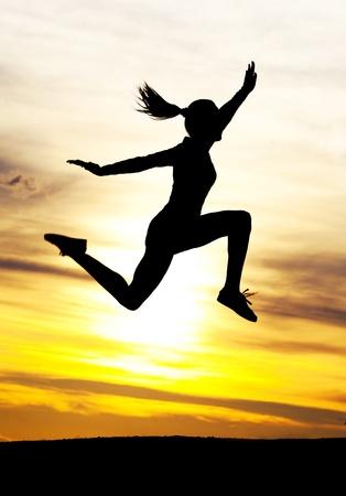 mujeres corriendo: Silueta de una hermosa mujer salta contra cielo amarillo con nubes al atardecer