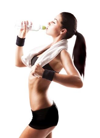 cuerpo femenino perfecto: agua potable deportivo mujer musculares aislado sobre fondo blanco Foto de archivo