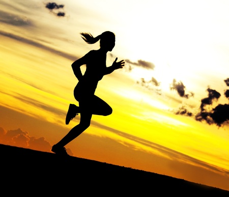 Silhouette of a beautiful woman running down the hill against yellow sky with clouds at sunset