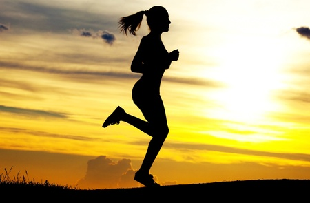 shadow woman: Silhouette of a beautiful running woman against yellow sky with clouds at sunset Stock Photo