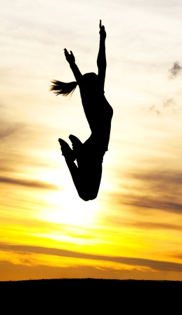 Silhouette of a young jumping woman against yellow sky with clouds at sunset photo