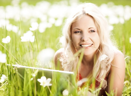 beautiful young blond woman with a laptop  in the park  on a warm summer day photo
