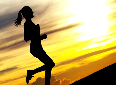 Silhouette of a beautiful woman running up the hill against yellow sky with clouds at sunset photo
