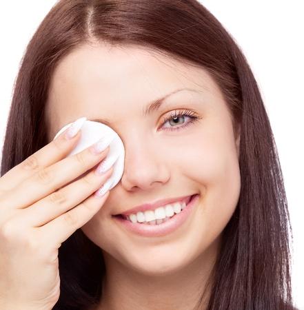 joven y bella mujer morena con almohadillas de algodón para quitar el maquillaje, aislado contra el fondo blanco