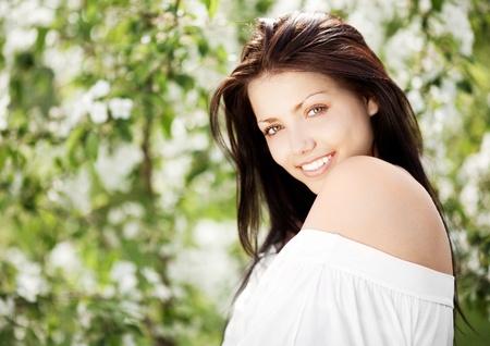 russian woman: beautiful young brunette woman standing near the apple tree Stock Photo